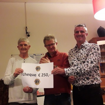Erik Boerma en Peter van Dijken overhandigen een cheque aan de vrijwilligers van het Bruin Cafe.
